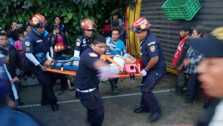 Bomberos Municipales Departamentales trasladan a uno de los heridos en el accidente del bus, en Santa María Cauque, Santiago Sacatepéquez. (Foto Prensa Libre: CBMD)