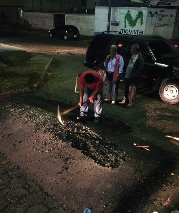Con una piocha una persona reduce la altura de uno de los túmulos en la 30 avenida de la zona 3, residencial Delco. (Foto Prensa Libre: Mynor Toc)