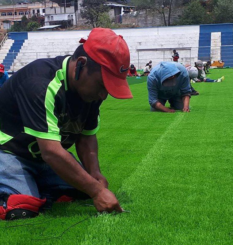 Empleados de la empresa contratada instala la gramilla sintética en el campo de futbol de Comitancillo. (Foto Prensa Libre: Whitmer Barrera)