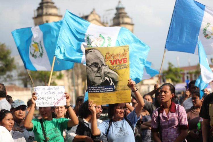 Entre las banderas de Guatemala sobresale un afiche que recuerda el asesinato de Juan Gerardi