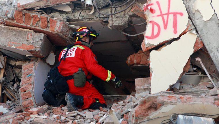 Un bombero peruano intenta escuchar una presunta persona atrapada en los escombros en la localidad de Manta. (Foto Prensa Libre: EFE).