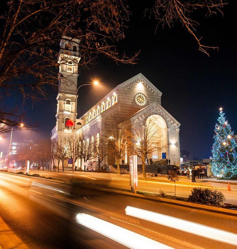 Varios automóviles pasan frente a la catedral de la Madre Teresa antes de la Misa de Gallo en Pristina. (AFP).
