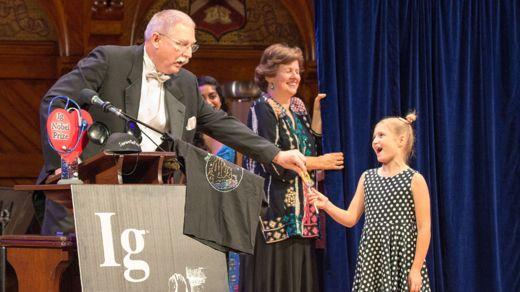 """El profesor David Wartinger durante su discurso de aceptación. La niña de 8 años Dorothea Hartig pemitía a cada ganador hablar solamente un minuto. Si se pasaban los interrumpía con el mensaje """"Please stop, I'm bored """", """"Por favor detente, estoy aburrida"""" (Foto Prensa Libre: ANNALS OF IMPROBABLE RESEARCH)."""