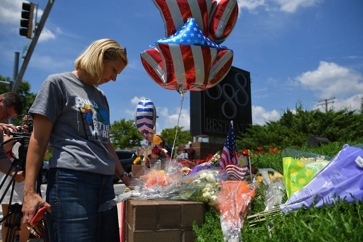 Personas colocan arreglos florales en honor de los periodistas muertos en Annapolis. (Foto Prensa Libre: AFP)