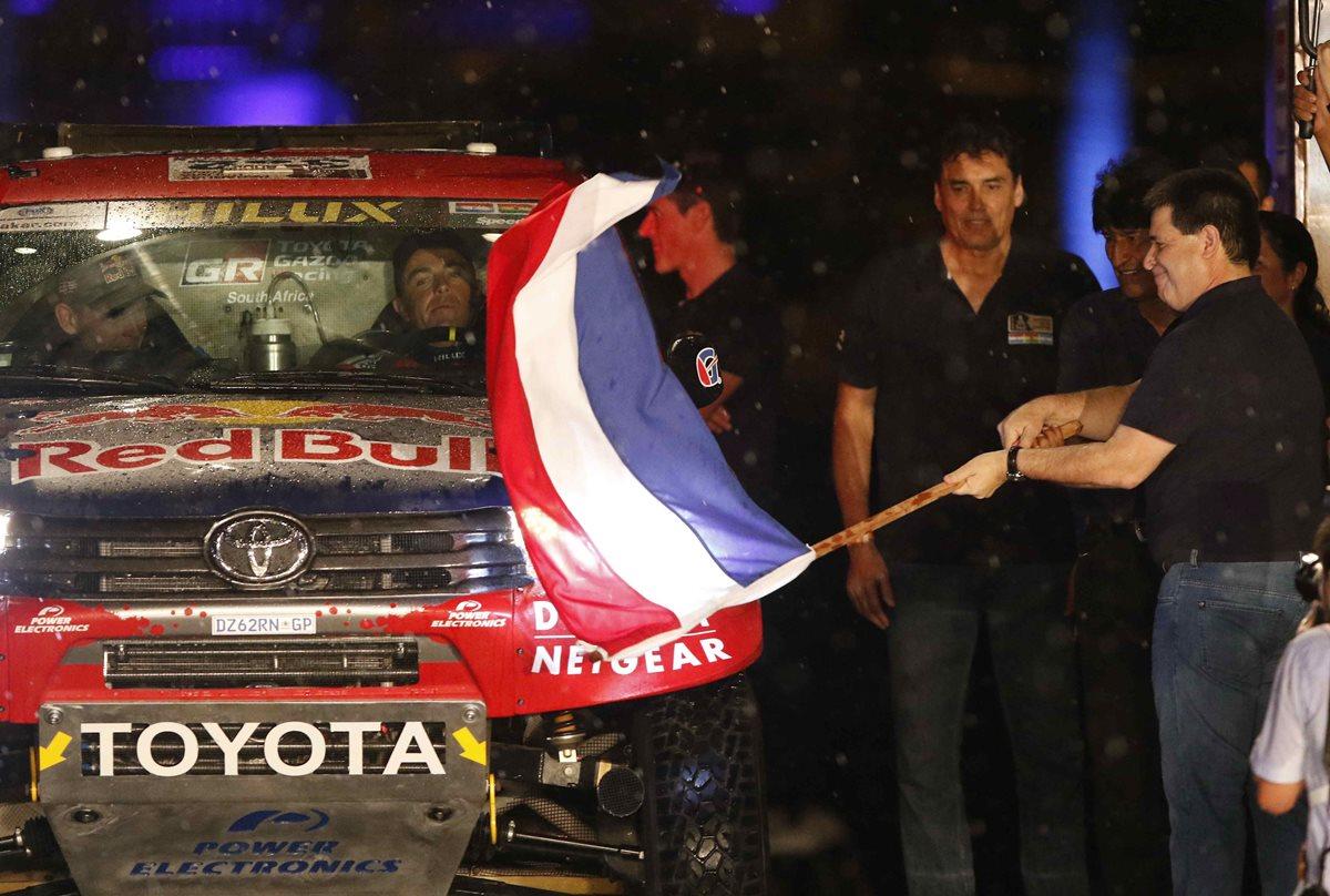 El presidente paraguayo, Horacio Cartes da el banderazo de salida al piloto sudafricano Giniel De Villiers, durante la largada del Rally Dakar 2017 en la ciudad de Asunción. (Foto Prensa Libre: EFE).