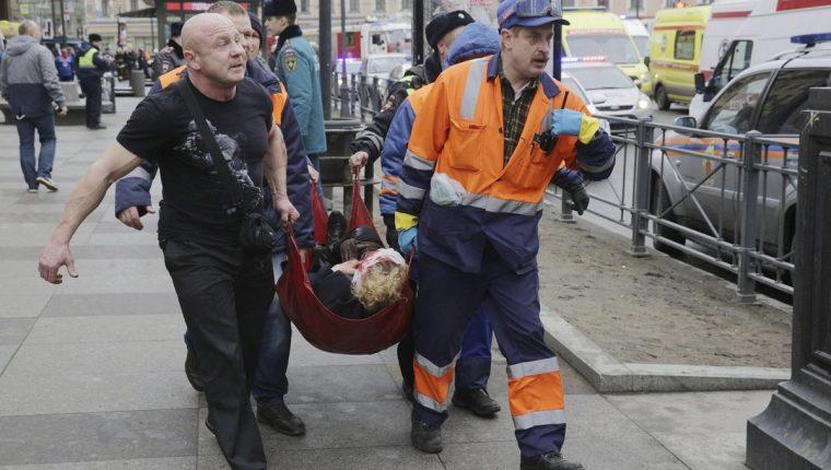 Bomberos y trabajadores de los servicios de emergencias transportan a una mujer, víctima del atentado terrorista ocurrido en el metro de San Petersburgo. (Foto Prensa Libre: EFE).