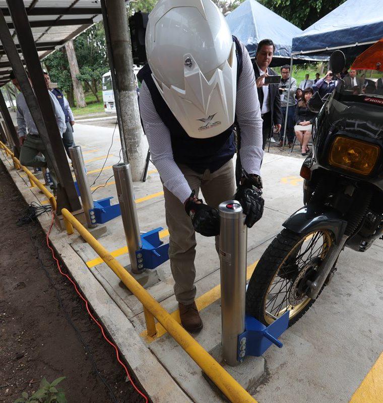 Un estudiante introduce la llave electrónica en el parquímetro y usa el sujetador para retener la motocicleta. (Foto Prensa Libre: Estuardo Paredes)