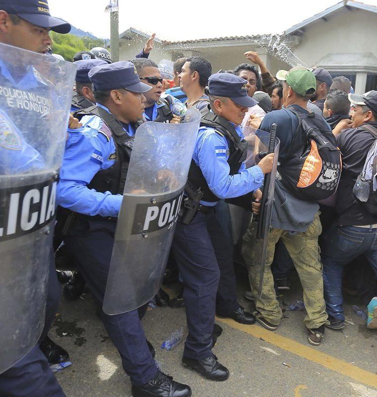 Centenares de migrantes hondureños intentan cruzar un retén policial para continuar su paso a Guatemala. (Foto Prensa Libre: EFE)