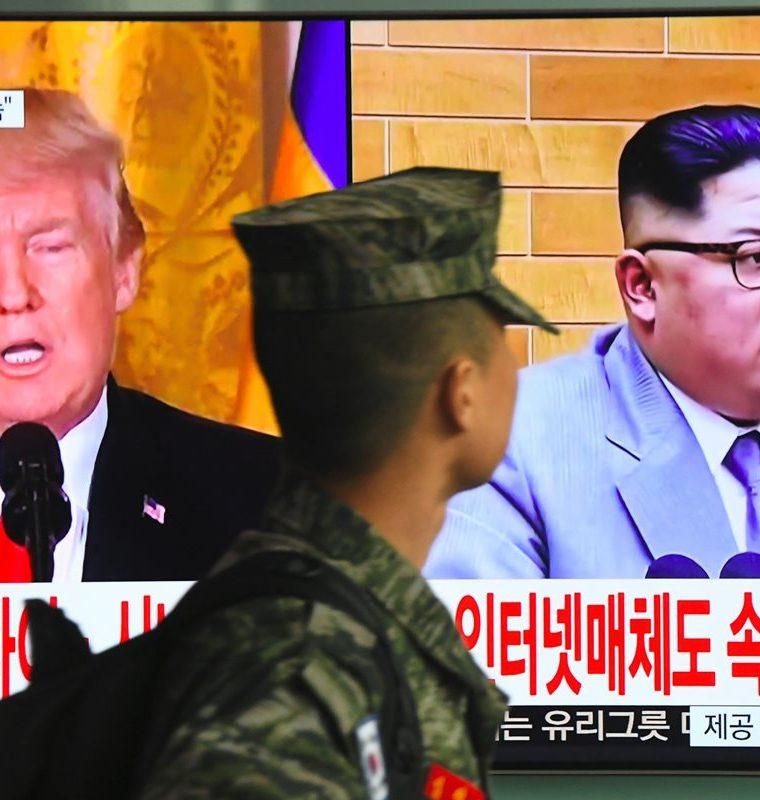 Un soldado surcoreano pasa frente a una pantalla de televisión que muestra imágenes del presidente estadounidense, Donald Trump (L) y el líder norcoreano, Kim Jong Un, en una estación de tren en Seúl.(AFP).