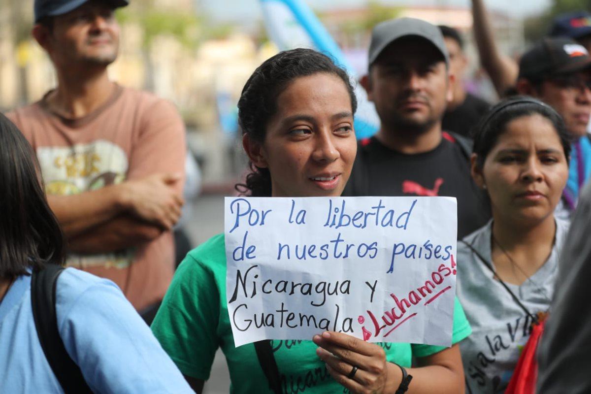 Algunos manifestantes portan pancartas frente al Palacio Nacional