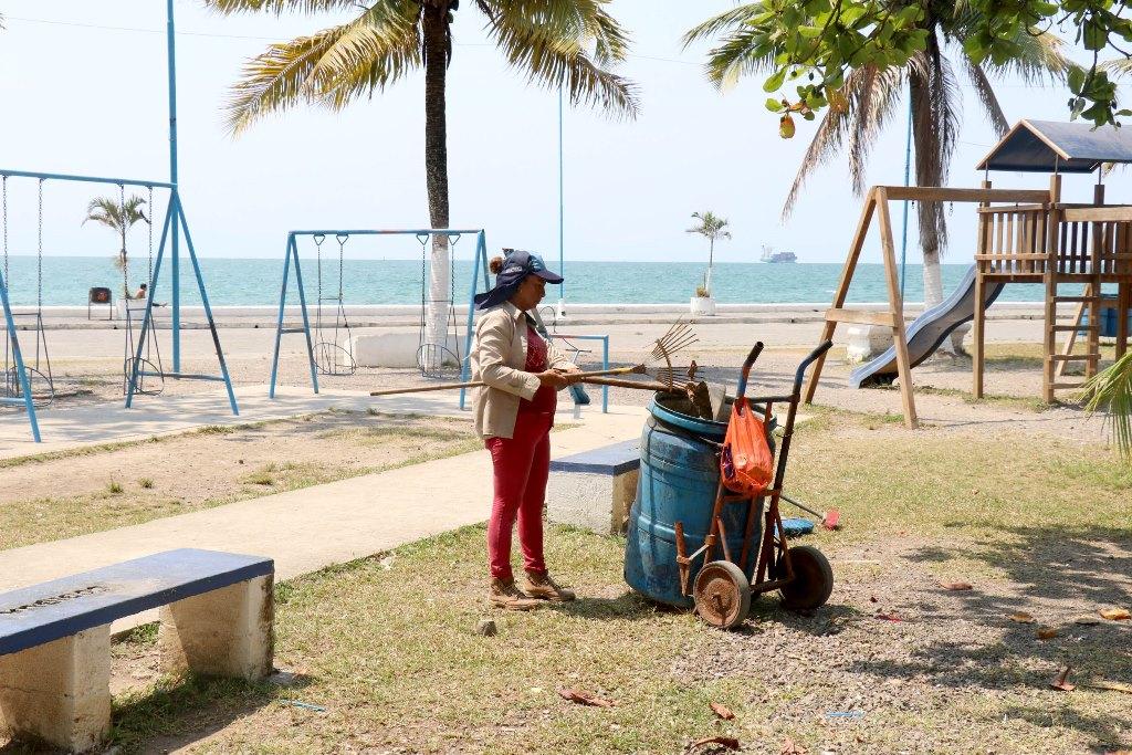 Trabajadora municipal limpia los alrededores del malecón de Puerto Barrios. (Foto Prensa Libre: Dony Stewart)