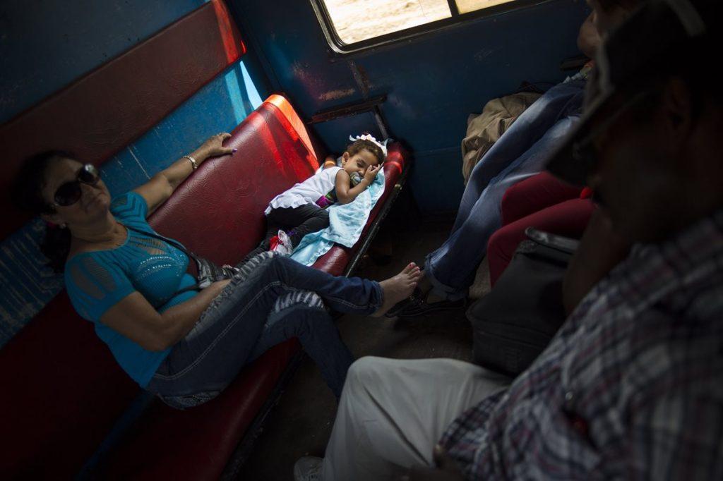Una mujer vigila el sueño de su hijo en el tren.