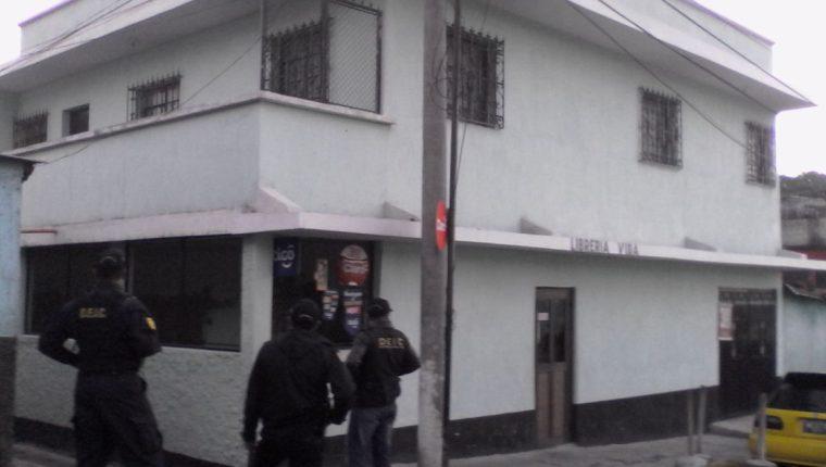 Agentes de la Deic controlar uno de los inmuebles allanados en la zona 6 de Mixco. (Foto Prensa Libre: Cortesía PNC)