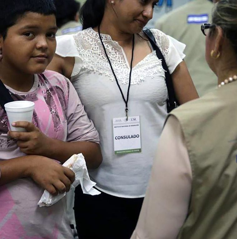 Personal del Consulado hondureño reciben a Mario Castellanos en el aeropuerto de San Pedro Sula. (Foto Prensa Libre: AFP)