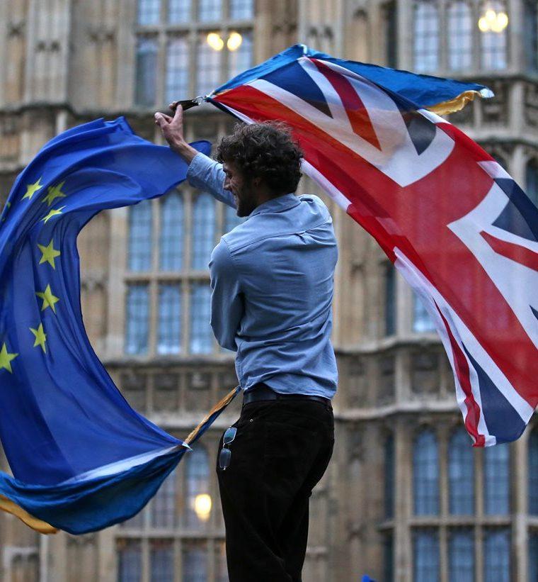 Un británico agita las banderas del Reino Unido y de la UE cerca del Parlamento en Londres. (AFP).