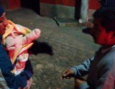 Vecino carga a bebé localizada en la ciudad de Quetzaltenango. (Foto Prensa Libre: Bomberos Voluntarios).