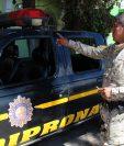 Agente de la Diprona muestra algunos de los daños que la turba causó a un autopatrulla en San Cristóbal Totonicapán. (Foto Prensa Libre: Édgar Domínguez)