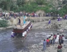 Devotos cargadores caminan descalzos para pasar el río con la imagen de Jesús Nazareno. (Foto Prensa Libre: Youtube)