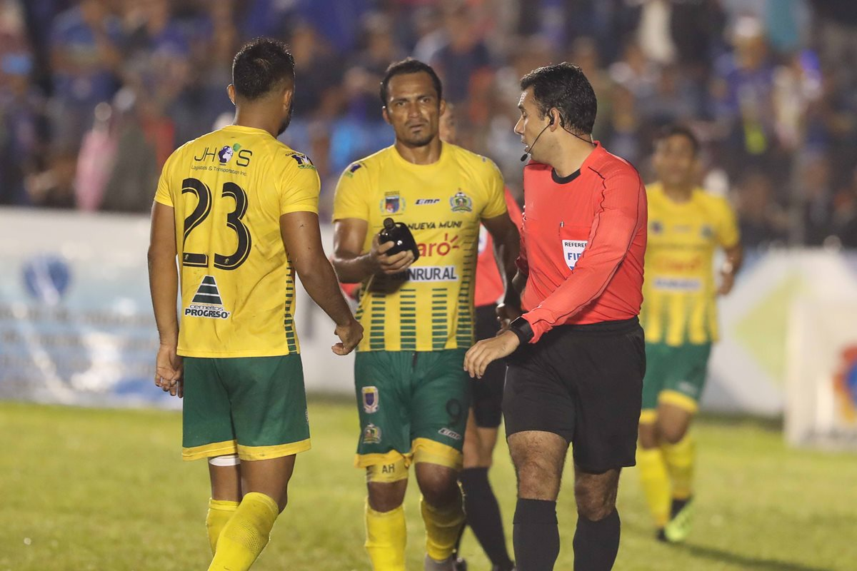 Ángel Rodríguez de Guastatoya le entrega al árbitro Escobar la botella de licor que le causo la herida en la cabeza. (Foto Prensa Libre: Hemeroteca PL)
