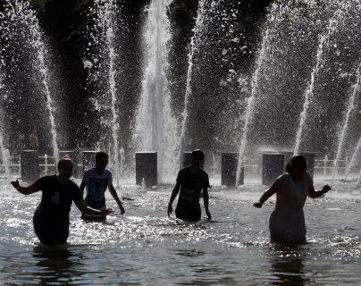 Varias personas se refrescan en una fuente del parque Gorki, en Moscú, Rusia. (Foto Prensa Libre:EFE)