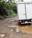 Un camión transita con dificultad por los grandes baches, en San Gabriel, San Antonio Palopó. (Foto Prensa Libre: Ángel Julajuj)