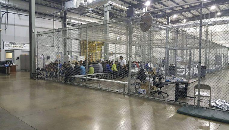 Varias personas que cruzaron la frontera ilegalmente en el sur de EE. UU. son detenidas en el Centro de Procesamiento Central en McAllen, Texas. (AFP)