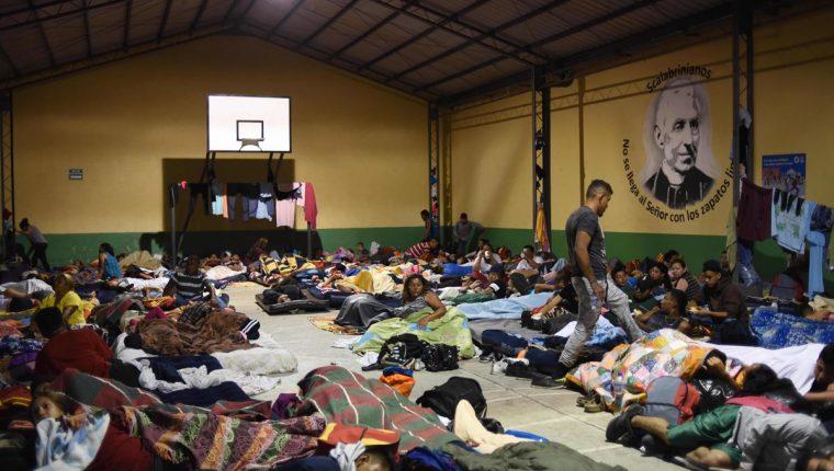 Hondureños duermen en la Casa del Migrante, zona 1, donde suelen pernoctar una noche para, al día siguiente, continuar su travesía hacia EE. UU. (Foto Prensa Libre: AFP)