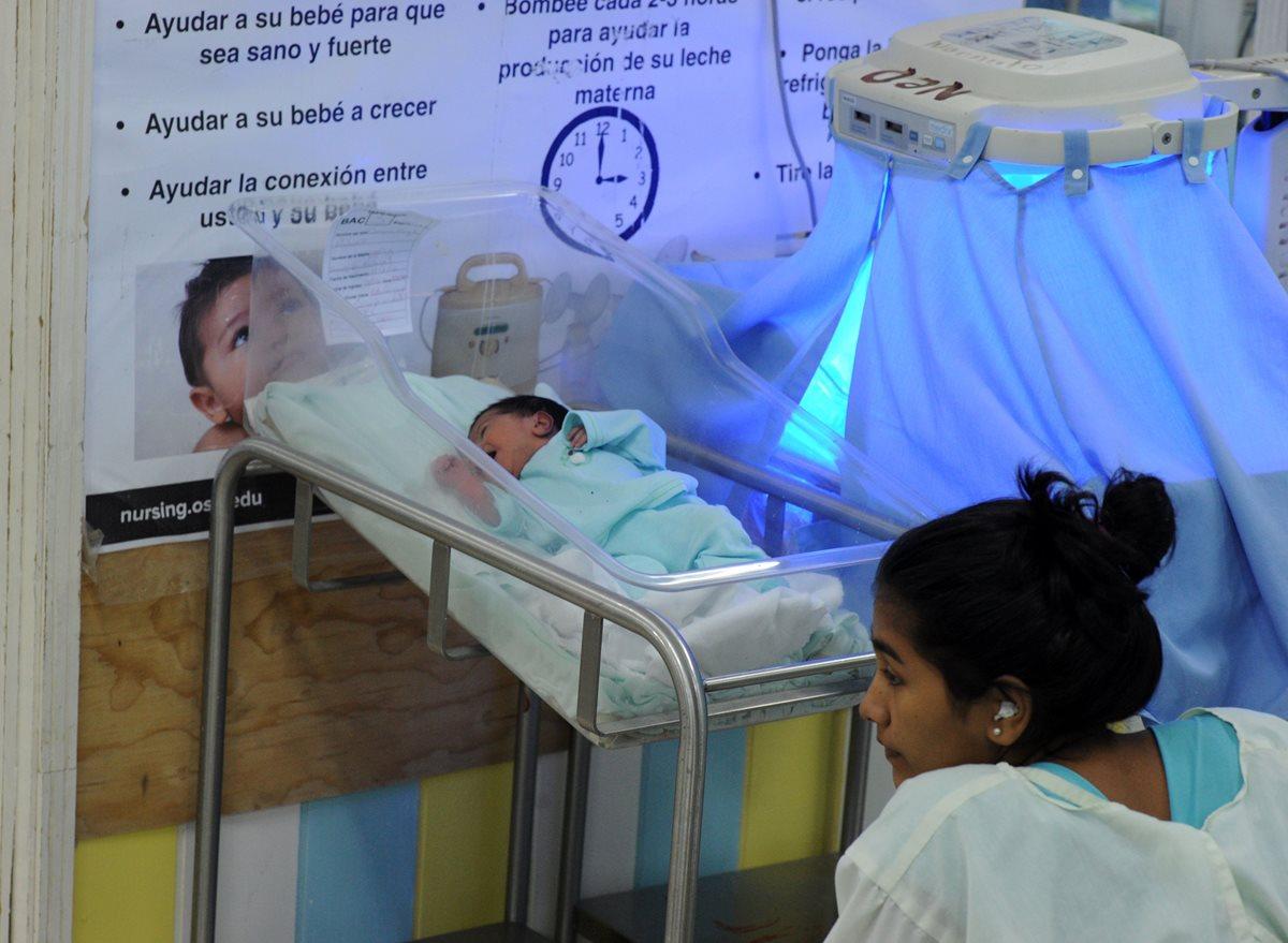 Una mujer observa a su hijo recién nacido en un hospital de Honduras. (Foto Prensa Libre: AFP).