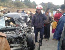 Vecinos observan el taxi en el que murieron dos personas al chocar contra tráiler, en el cruce a Concepción Tutuapa y Sipacapa, San Marcos. (Foto Prensa Libre: Whitmer Barrera)