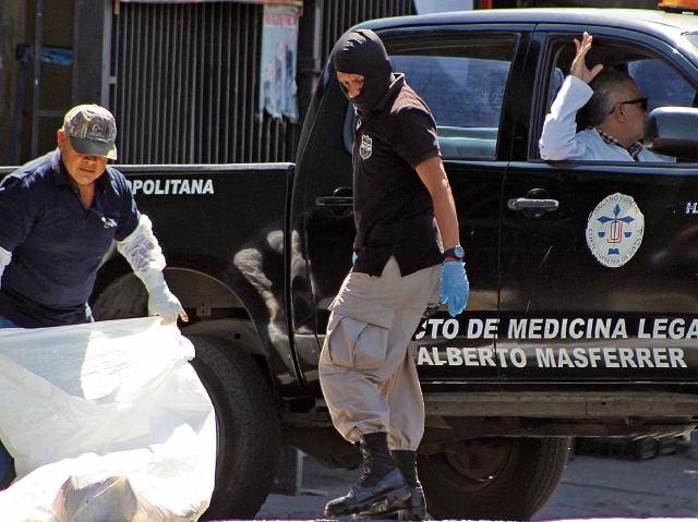 Efectivos de la Policía forense salvadoreña trabajan en la escena del crimen, donde un joven fue asesinado por pandilleros, en San Salvador, El Salvador. (Foto Prensa Libre: AFP)