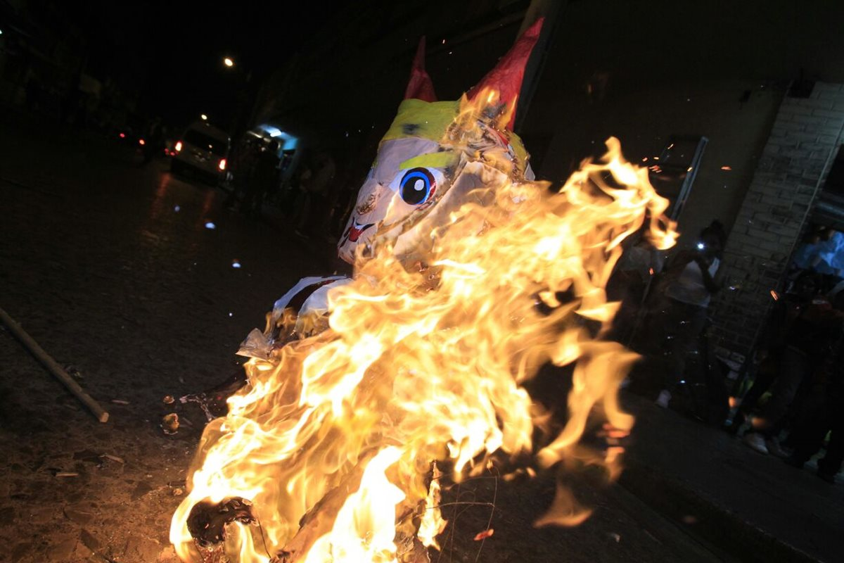 Una piñata con el rostro de Donald Trump fue quemada por vecinos en el parque Colón, zona 1 capitalina. (Foto Prensa Libre: Carlos Hernández)