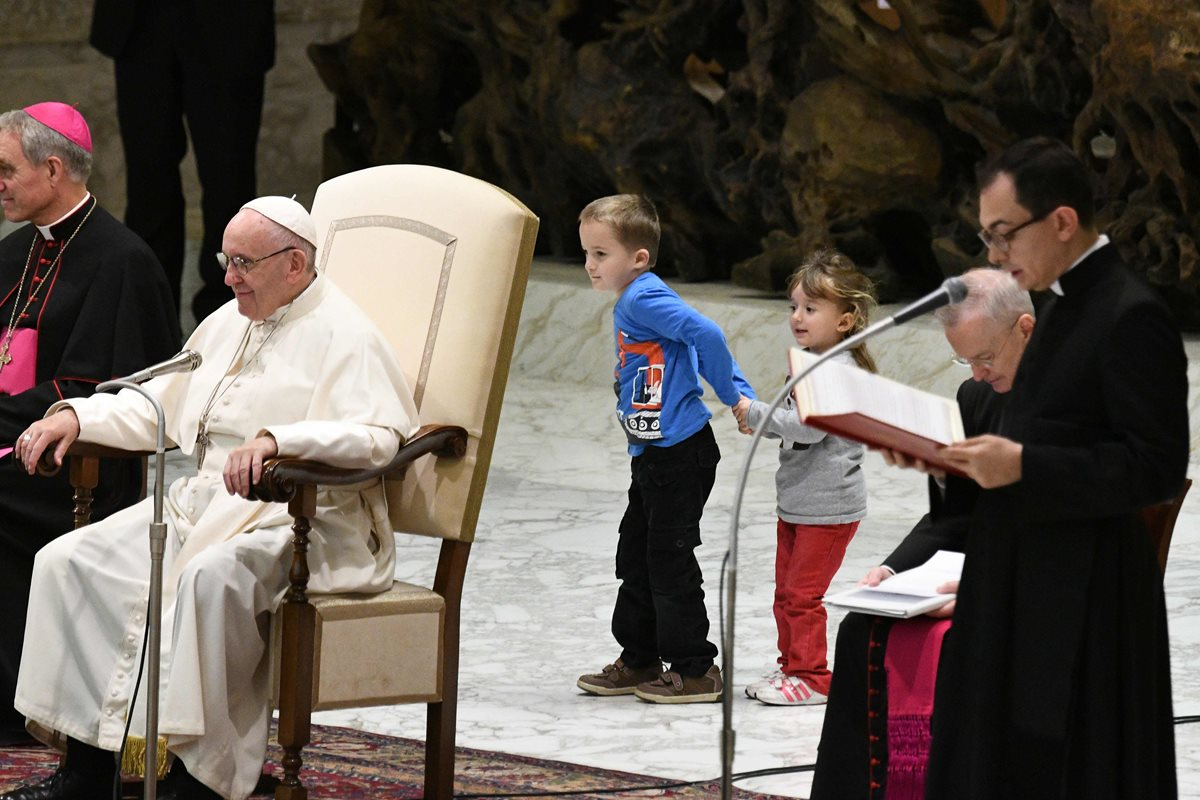 El pequeño Wenzel Eluney  junto a su hermana, juegan detrás del Papa Francisco.