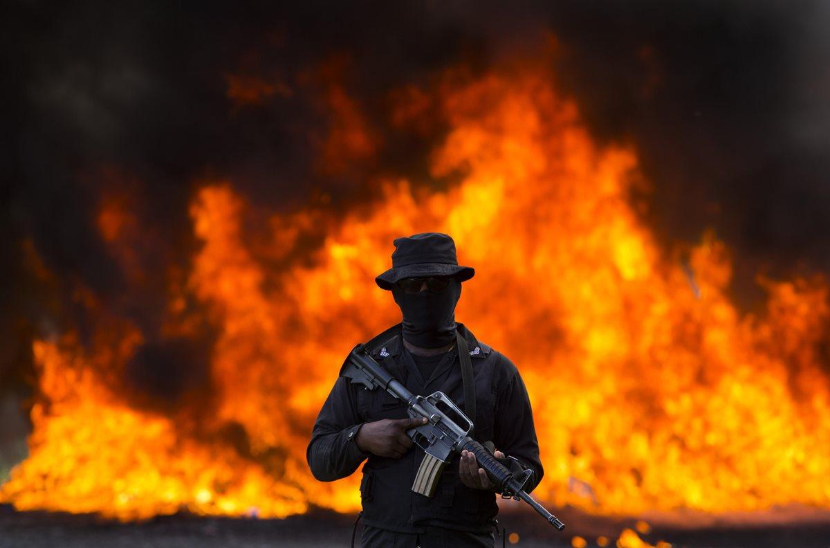 Cientos de kilos de diferentes drogas son incinerados en República Dominicana, mientras un soldado resguarda el área. (Foto Prensa Libre: EFE)