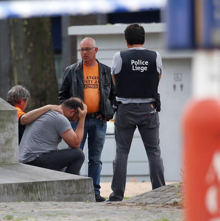 Agentes de la Policía belga consuelan a un transeúnte afectado por la balacera en Lieja, Bélgica. (EFE).