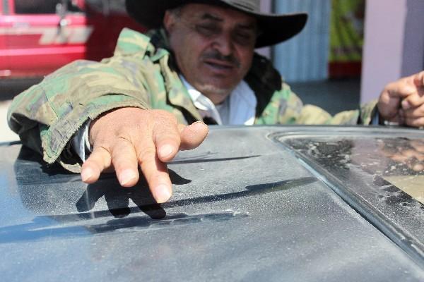 Vecino muestra  la  ceniza en un vehículo.