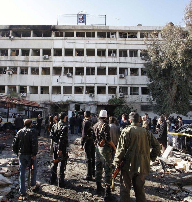 Personas permanecen en el sitio de un atentado con bomba en un edificio en Damasco, Siria, el 23 de diciembre de 2011. (Foto: AP)