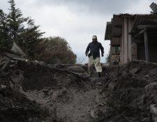 Un residente camina entre los escombros en la población de El Rodeo, la cual aún permanece sepultada tras la erupción del Volcán de Fuego. (Foto Prensa Libre: EFE)