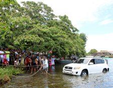 Personas observaron la extracción del vehículo que cayó al Lago de Izabal, donde una mujer falleció por causas que se investigan. (Foto Prensa Libre: Dony Stewart)
