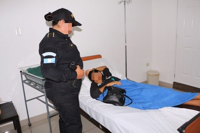 Agente de la PNC custodia a Verónica Lima, madre de la bebé. (Foto Prensa Libre: PNC).
