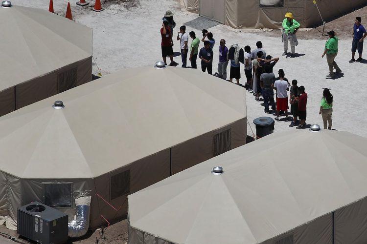 Un grupo de menores son formados a la par de las carpas del campamento.