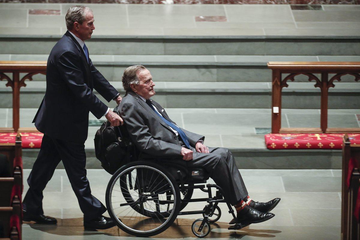 George W. Bush (izq.), expresidente de los EEUU, lleva a su padre, George H.W. Bush, también expresidente de los EEUU, en una silla de ruedas durante el funeral de Barbara Bush. (Foto Prensa Libre: DPA)