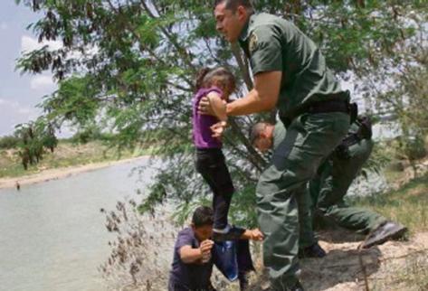 Una niña  es rescatada por agentes después al cruzar el río en la  frontera entre México y EE. UU. Cientos de migrantes indocumentados,  muchos de ellos niños, han llegado de manera ilegal a EE. UU., lo cual  ha causado una crisis humanitaria.
