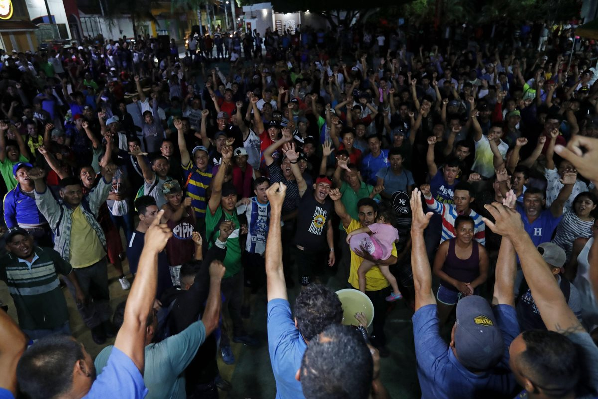 Migrantes hondureños intentaron agredir a un supuesto estafador en Tecún Umán, frontera con México, un pastor evangélico intenta calmarlos. (Foto Prensa Libre: EFE)
