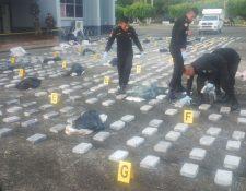 Agentes antinarcóticos contabilizan la droga incautada en aguas del Caribe. (Foto Prensa Libre: PNC)
