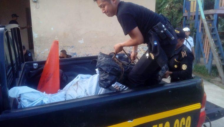 Agente de la Policía Nacional Civil ayuda con el traslado de los cuerpos de las víctimas hacia la morgue del Inacif en Zacapa. (Foto Prensa Libre: Mario Morales)
