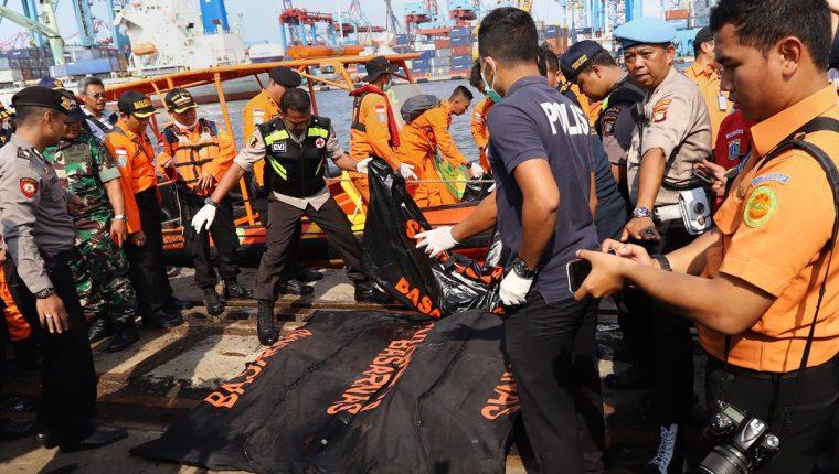 Socorristas rescatan los primeros cuerpos de las víctimas del accidente aéreo. (Foto Prensa Libre: AFP)