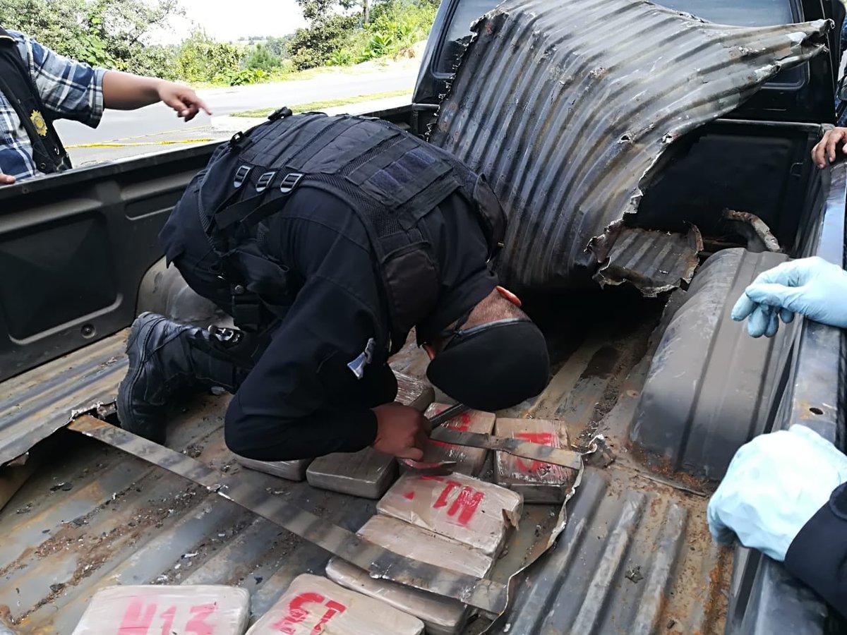Un agente antinarcóticos extrae del doble fondo de la palangana del picop interceptado en la ruta interamericana, los paquetes con cocaína. (Foto Prensa Libre: Policía Nacional Civil)