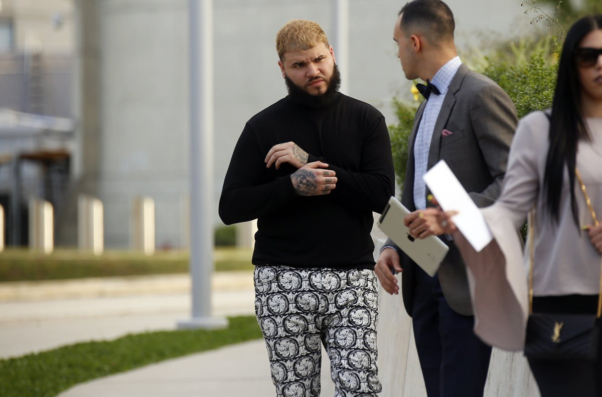 El reguetonero puertorriqueño Carlos Efrén Reyes Rosado, conocido como Farruko, conversa con un hombre a su salida en libertad condicional este miércoles (Foto Prensa Libre: EFE)