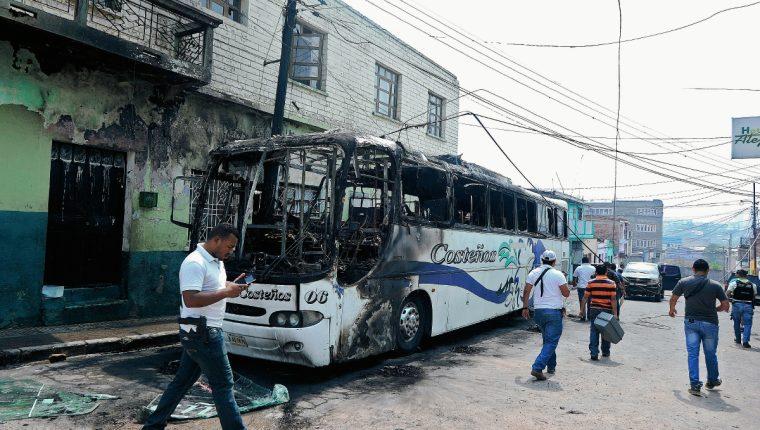 """Investigadores observan el bus que fue incendiado por pandilleros el jueves último porque no pagaron a tiempo el """"impuesto de guerra"""", que les exigen para circular en Tegucigalpa. (Foto Prensa Libre: AFP)."""