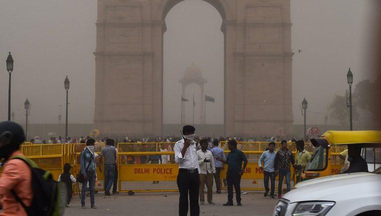 Un policía de tránsito indio se cubre la cara mientras está de servicio durante una tormenta de polvo en Nueva Delhi.(Foto Prensa Libre:AFP).